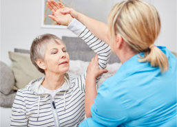 caregiver giving a physical therapy to elderly