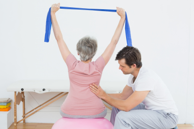 physical therapist assisting the elder woman doing her exercise
